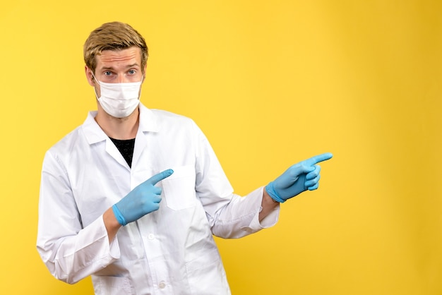 Вид спереди мужчина-врач на желтом фоне пандемического здоровья covid- вируса
