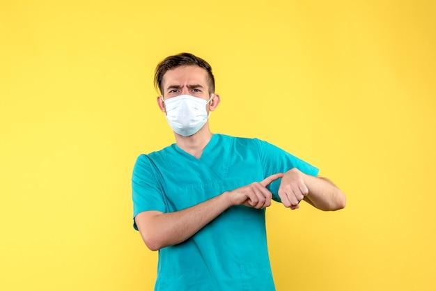 Vista frontale del medico maschio che punta il polso sulla parete gialla