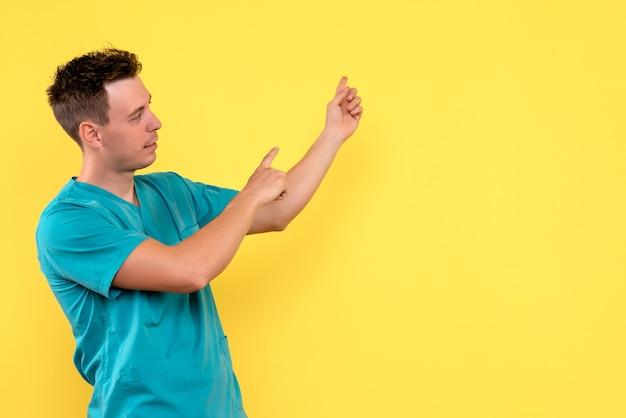 Vista frontale del medico maschio che punta sulla parete gialla