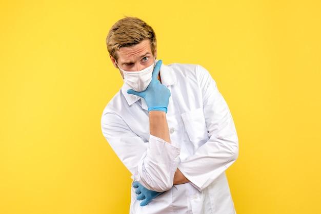 Вид спереди мужской доктор позирует на желтом фоне пандемический медик здоровья covid- вируса