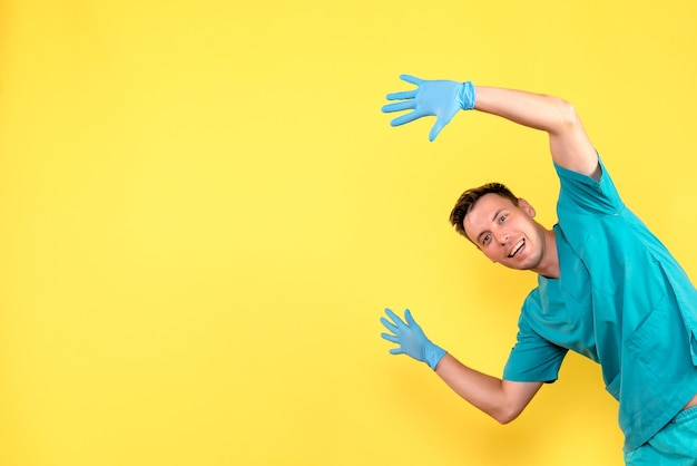 Front view of male doctor posing with blue gloves on yellow wall