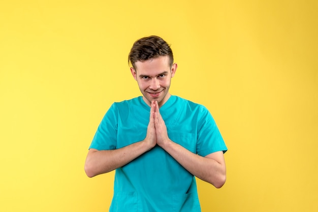 Vista frontale del medico maschio nella posa di preghiera sulla parete gialla