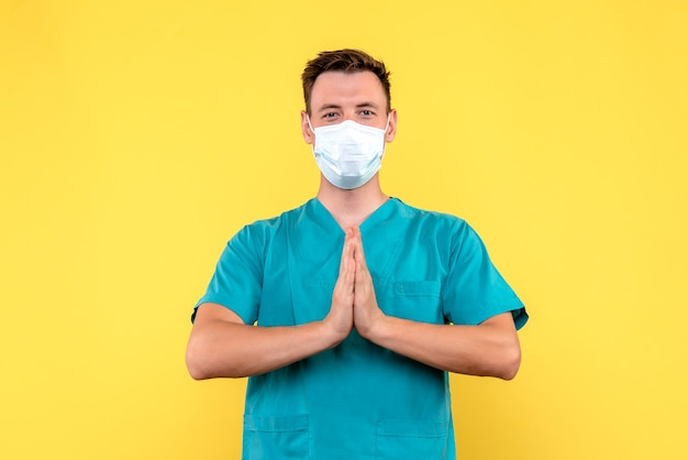 Vista frontale del medico maschio che prega sulla parete gialla