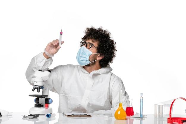 Medico maschio di vista frontale in tuta protettiva e maschera che tiene l'iniezione su bianco