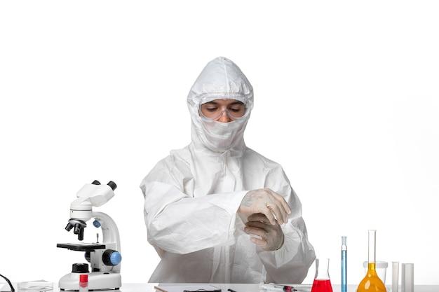 Medico maschio di vista frontale in vestito protettivo e con la mascherina appena che si siede sullo spazio bianco