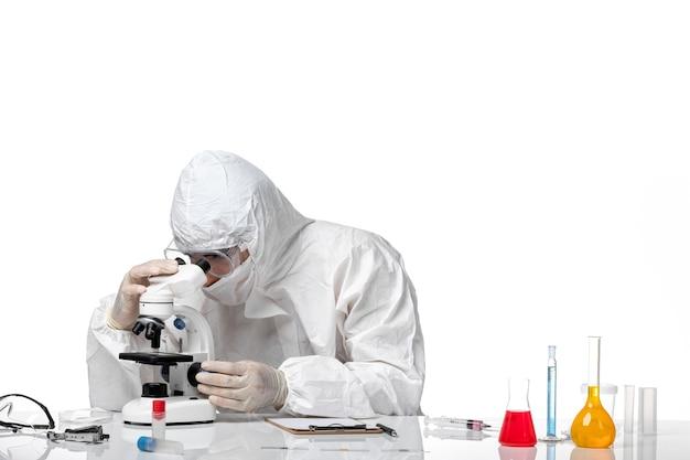 Medico maschio vista frontale in tuta protettiva e con maschera utilizzando il microscopio sullo spazio bianco