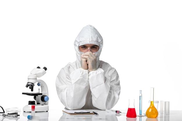 Medico maschio vista frontale in tuta protettiva e con maschera su uno spazio bianco