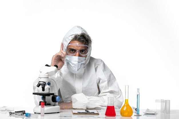 Front view male doctor in protective suit and with sterile mask raising his finger on white