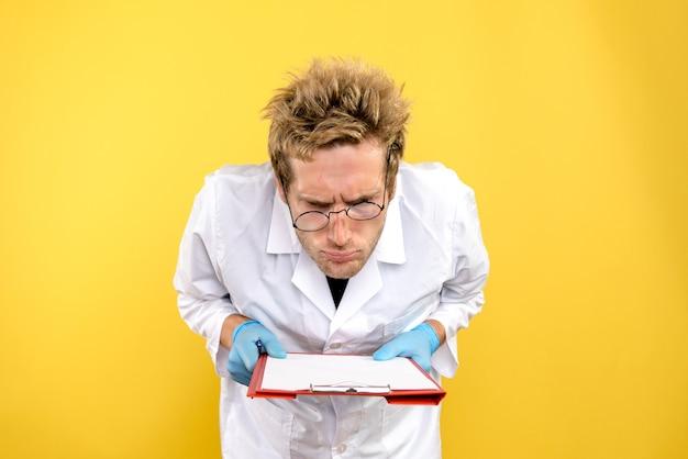黄色の背景の健康covid-人間のメモを読んで正面図男性医師