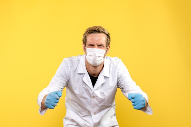 Medico maschio vista frontale che si rallegra in maschera su sfondo giallo virus pandemia covid-salute