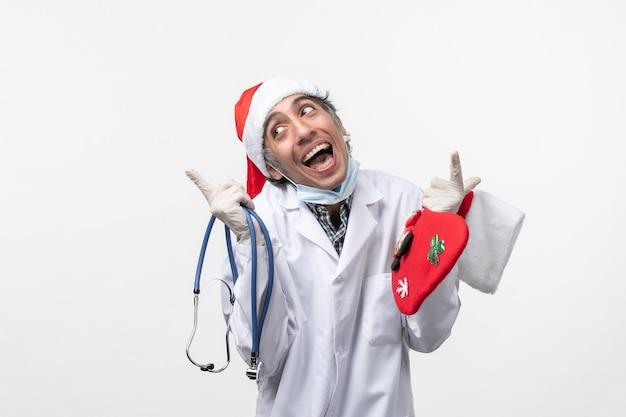 Вид спереди мужской доктор радуется на белом столе вируса covid праздничное здоровье