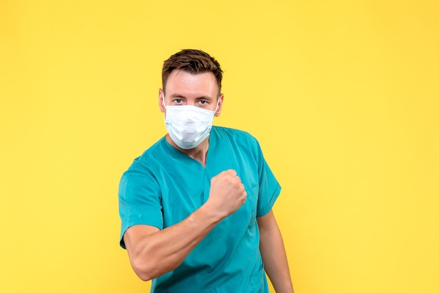 Front view of male doctor rejoicing on yellow wall