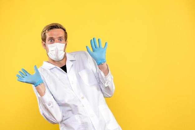 正面図男性医師は黄色の背景の健康covidパンデミックウイルスを怖がっています
