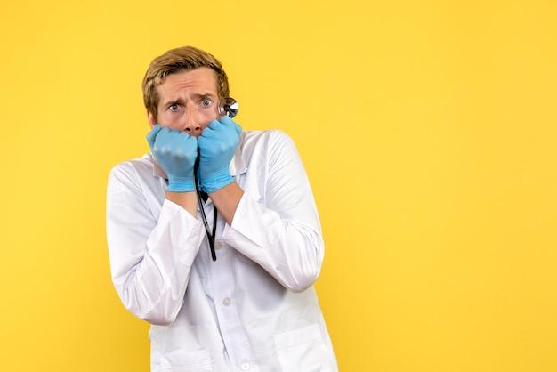 正面図男性医師は黄色の背景の健康人間ウイルス薬を怖がっています