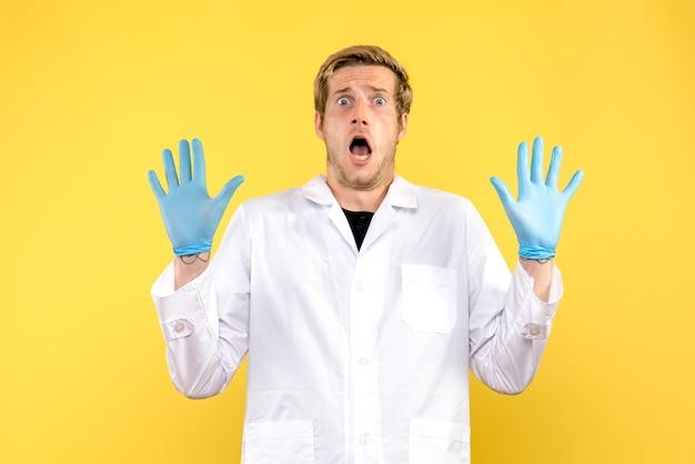 正面図男性医師は黄色の背景に怖がっている人間の薬の感情