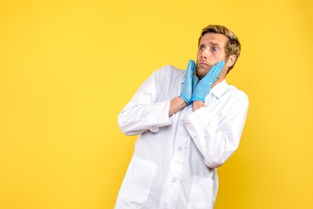 正面図男性医師は黄色の背景に怖がっている薬の健康covidパンデミック