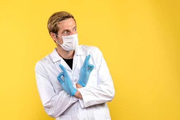 正面図男性医師は黄色の背景パンデミックcovid-健康ウイルスを怖がっています