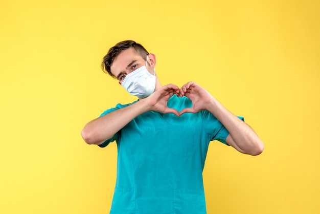 Front view of male doctor sending love in mask on yellow wall
