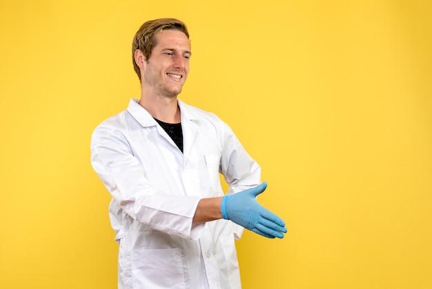 Vista frontale maschio medico stringe la mano su sfondo giallo salute medico covid-pandemia