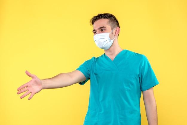 Vista frontale del medico maschio che agitano le mani sulla parete gialla