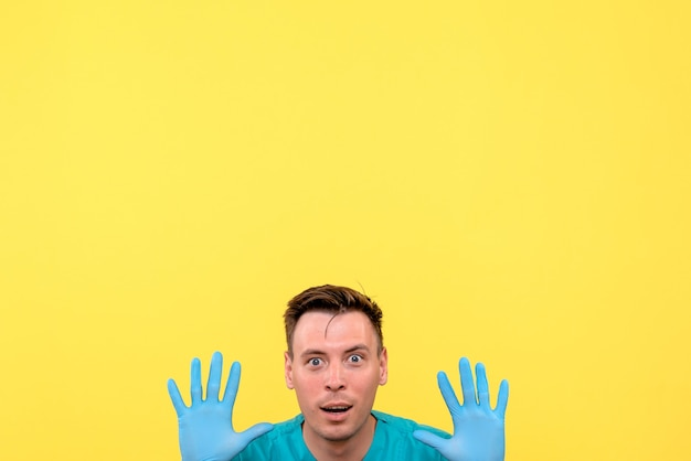 Front view of male doctor sitting with excited face on yellow wall