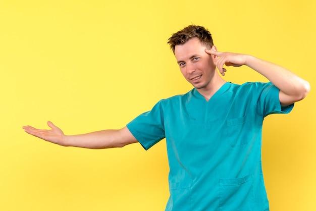 Vista frontale del medico maschio leggermente sorridente sulla parete gialla