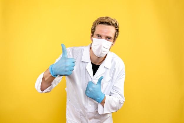 Вид спереди мужской доктор улыбается в маске на желтом фоне пандемический медик covid-