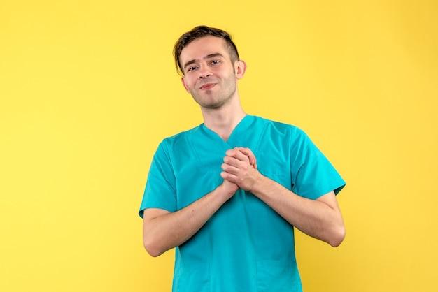 Vista frontale del medico maschio sorridente su un muro giallo chiaro