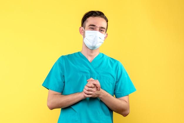 Vista frontale del medico maschio sorridente nella maschera sulla parete gialla