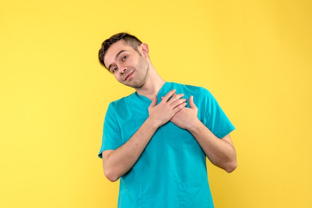Front view of male doctor smiling on yellow wall