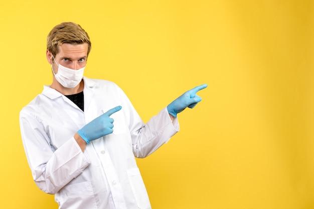 Medico maschio vista frontale in maschera sterile su sfondo giallo covid-medico di salute pandemica