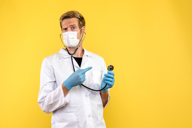 Front view male doctor in sterile mask on yellow background pandemic virus covid health