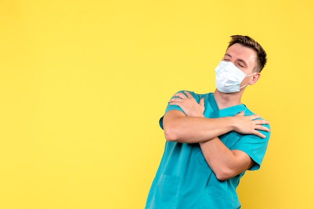 Front view of male doctor in sterile mask on the yellow wall
