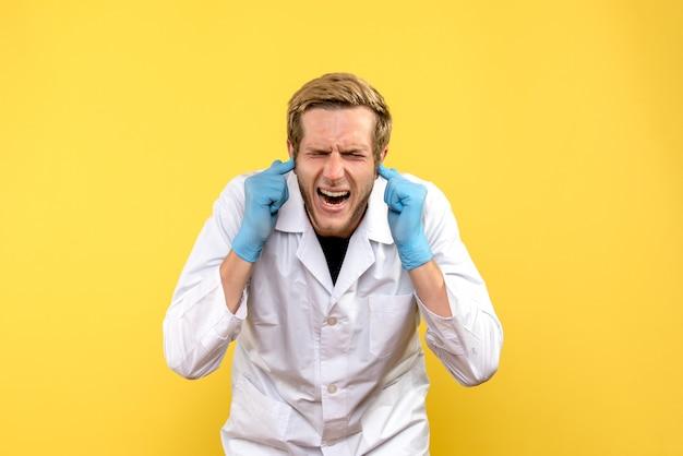 黄色の背景に耳を突き刺している正面図の男性医師