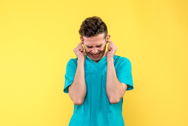 Front view of male doctor stucking his ears on yellow wall
