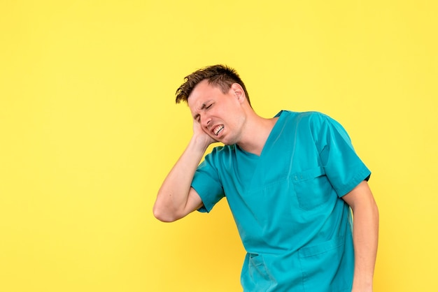 Front view of male doctor suffering from head pain on yellow wall