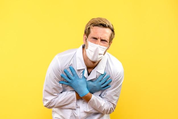 Vista frontale medico maschio che soffre di dolore su sfondo giallo salute covid-medic pandemia
