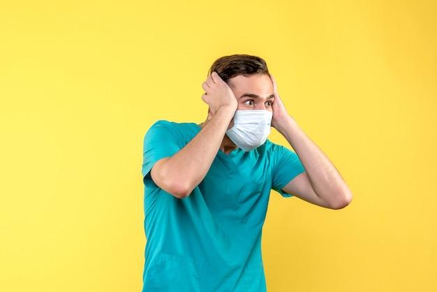 Vista frontale del medico maschio sorpreso in maschera sulla parete gialla