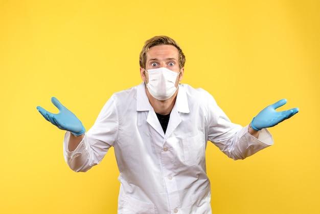 Вид спереди мужской доктор удивлен на желтом фоне пандемический медик здоровья covid