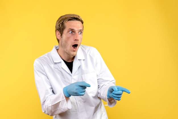 Medico maschio vista frontale sorpreso su sfondo giallo covid-medico ospedale umano