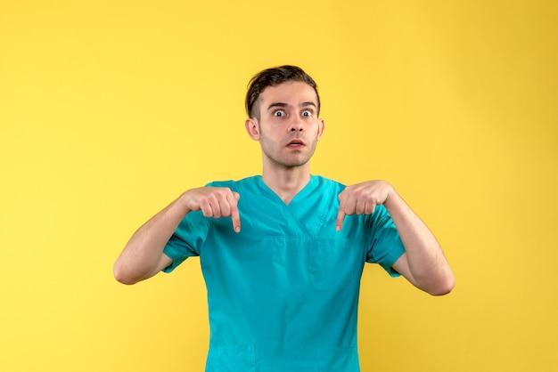 Vista frontale del medico maschio sorpreso sulla parete gialla