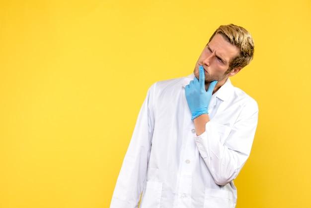 Вид спереди мужской доктор думает на желтом фоне человеческий медик covid- эмоции