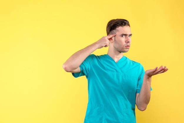 Vista frontale del medico maschio che pensa sulla parete gialla
