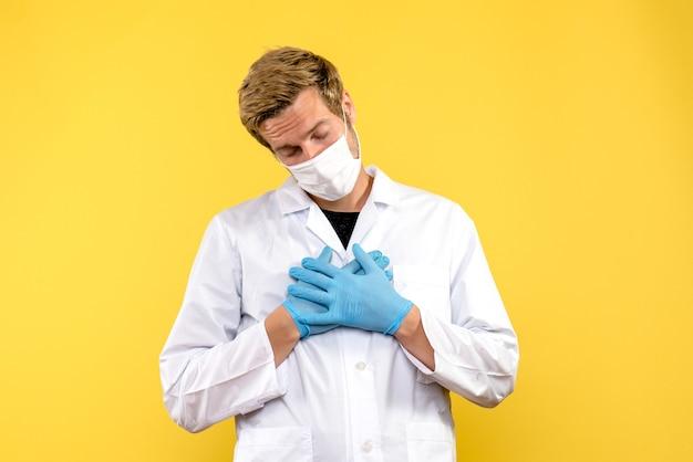 黄色の背景に疲れた正面図男性医師パンデミックメディックヘルスコビッドウイルス