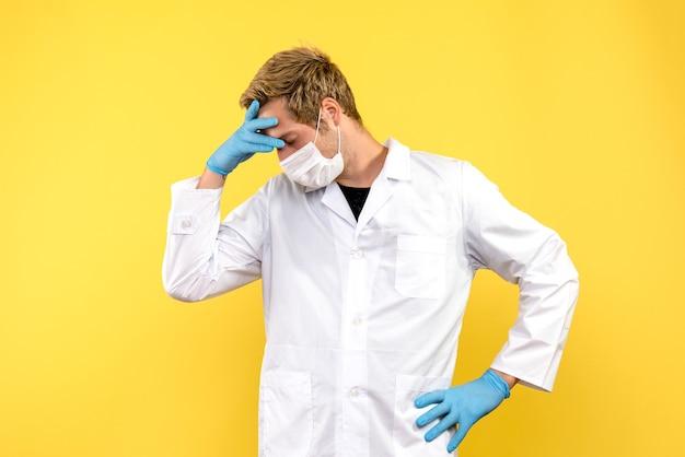 Vista frontale medico maschio stanco su sfondo giallo salute medic pandemia covid-