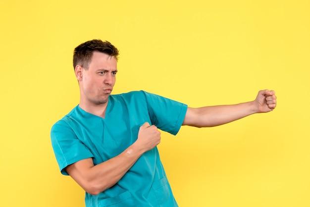 Vista frontale del medico maschio che prova a ballare sulla parete gialla