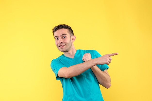 Front view of male doctor very excited on yellow wall