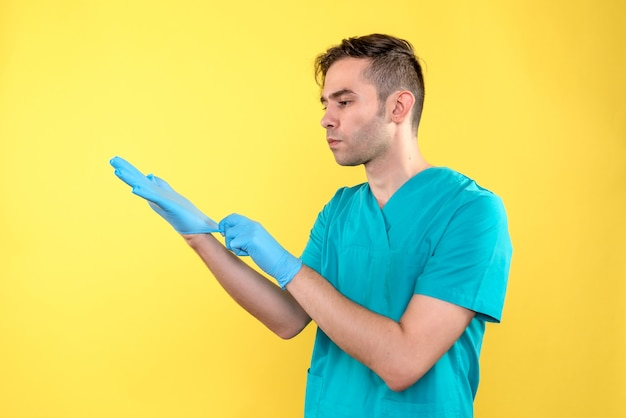 Vista frontale del medico maschio che indossa guanti blu sulla parete gialla