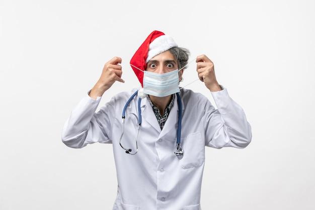 白い壁にマスクを身に着けている正面図男性医師年末年始ウイルスcovid