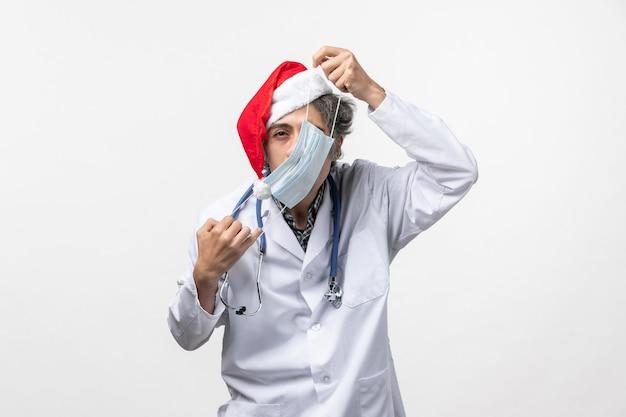 Mascherina da portare del medico maschio di vista frontale sul virus di festa di capodanno della parete bianca